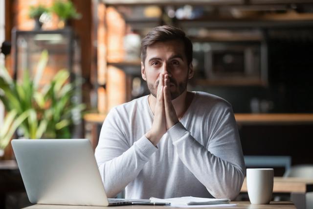 パソコンを前に考え事をしている男性