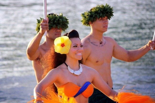 フラダンスの恰好をした女性と二人の男性
