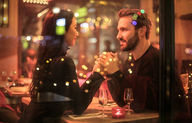 男女がお酒を飲みながら手を繋ぎ合っている