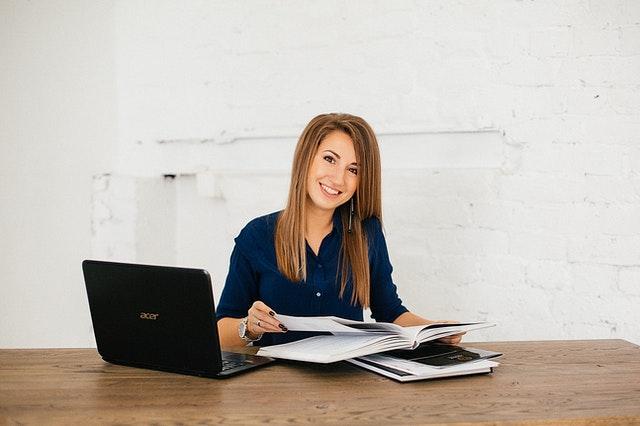 袖の長い青いシャツを着た女性が黒いパソコンの前に座っている