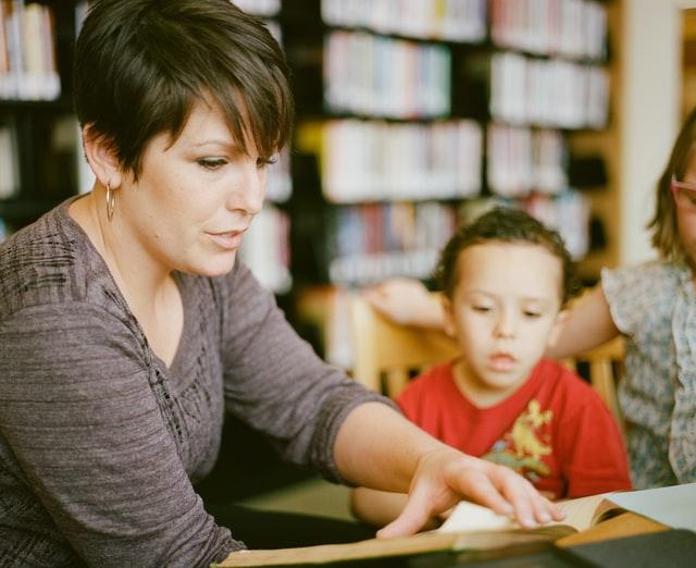 子供に本を読んでいる女性