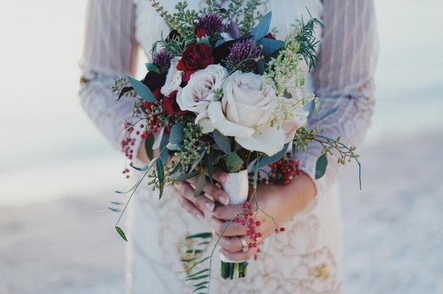 赤や白のバラのブーケットを持った女性