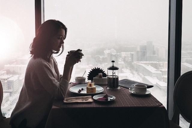 窓際の席でお茶を飲む女性