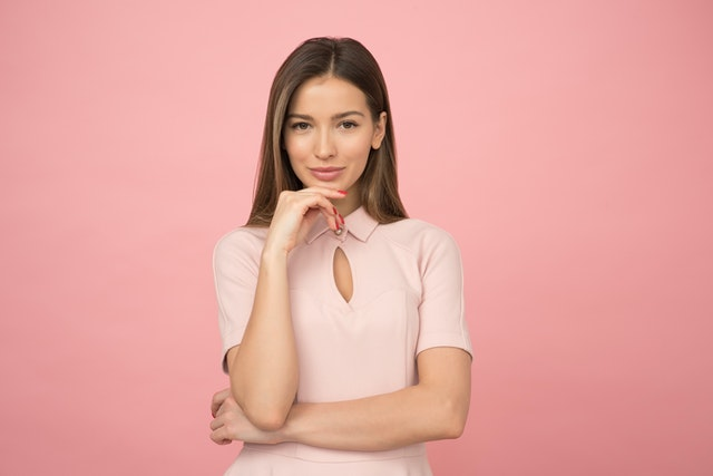 ピンクの服を着て、軽く考え込む女性