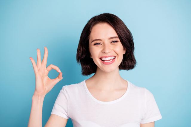 明るく鮮やかな青色背景に笑顔でグーサインを出す女性