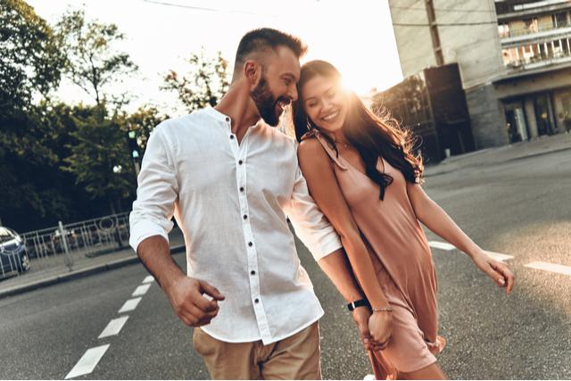 手をつなぎながら笑顔で歩く男女